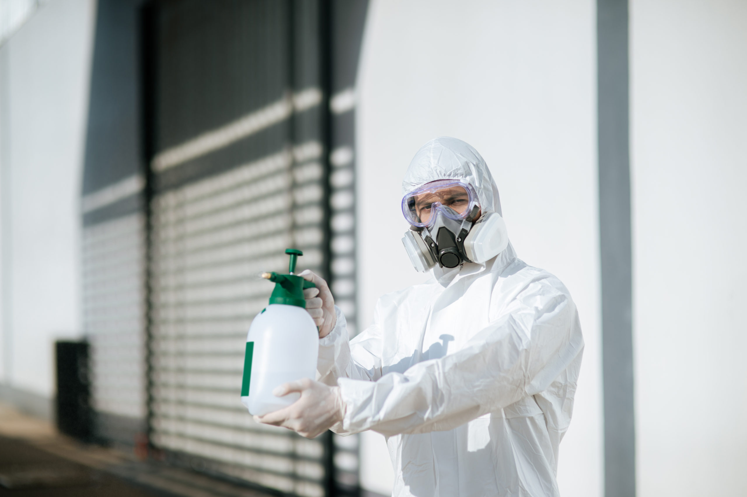 Disinfection specialist in PPE suit performing public decontamin