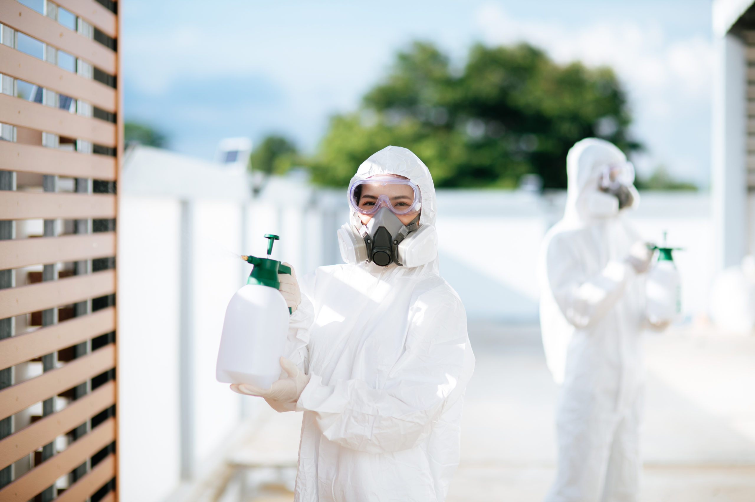 Disinfection specialist team in PPE suit performing public decon