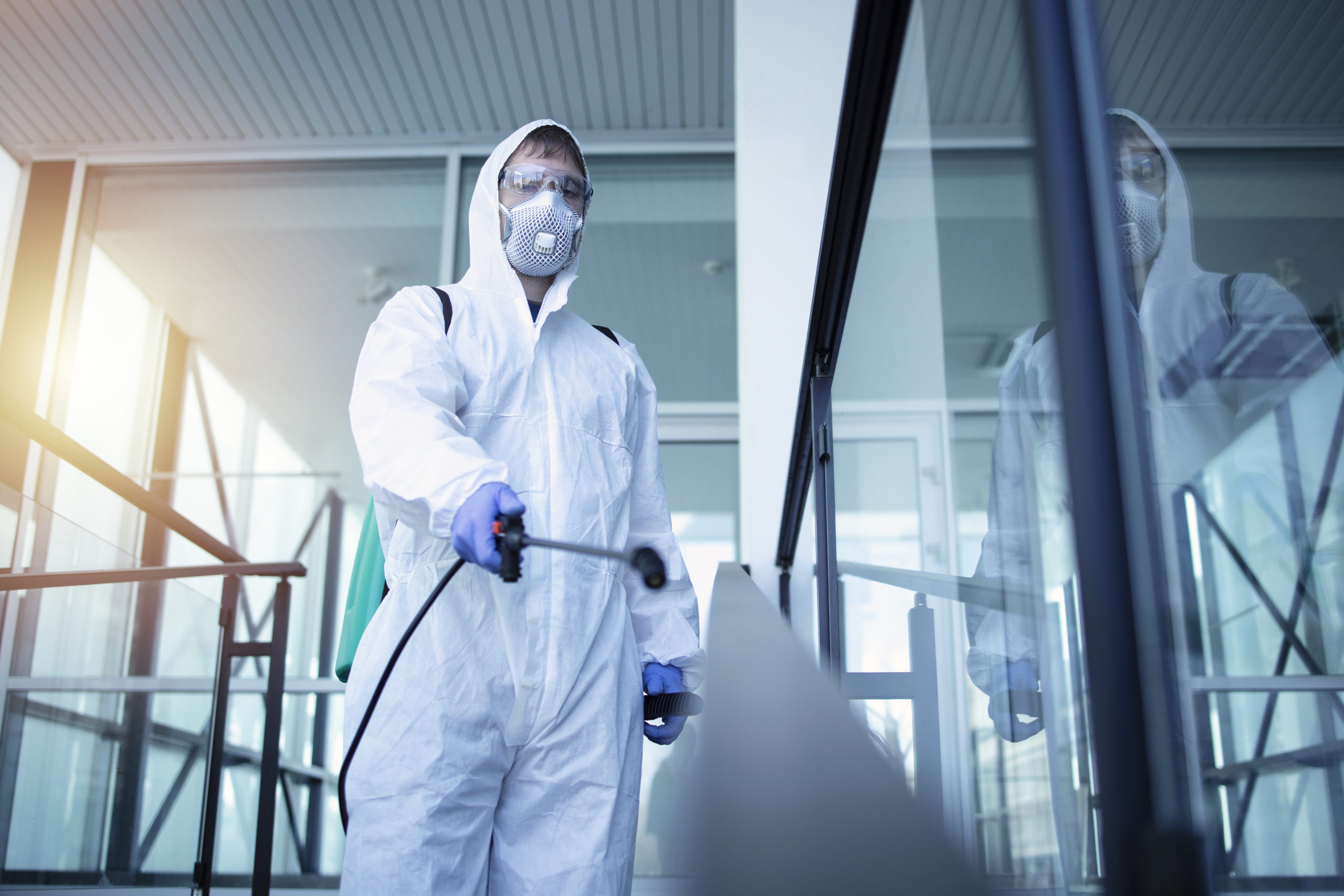 Person in white chemical protection suit doing disinfection of public areas to stop spreading highly contagious corona virus.