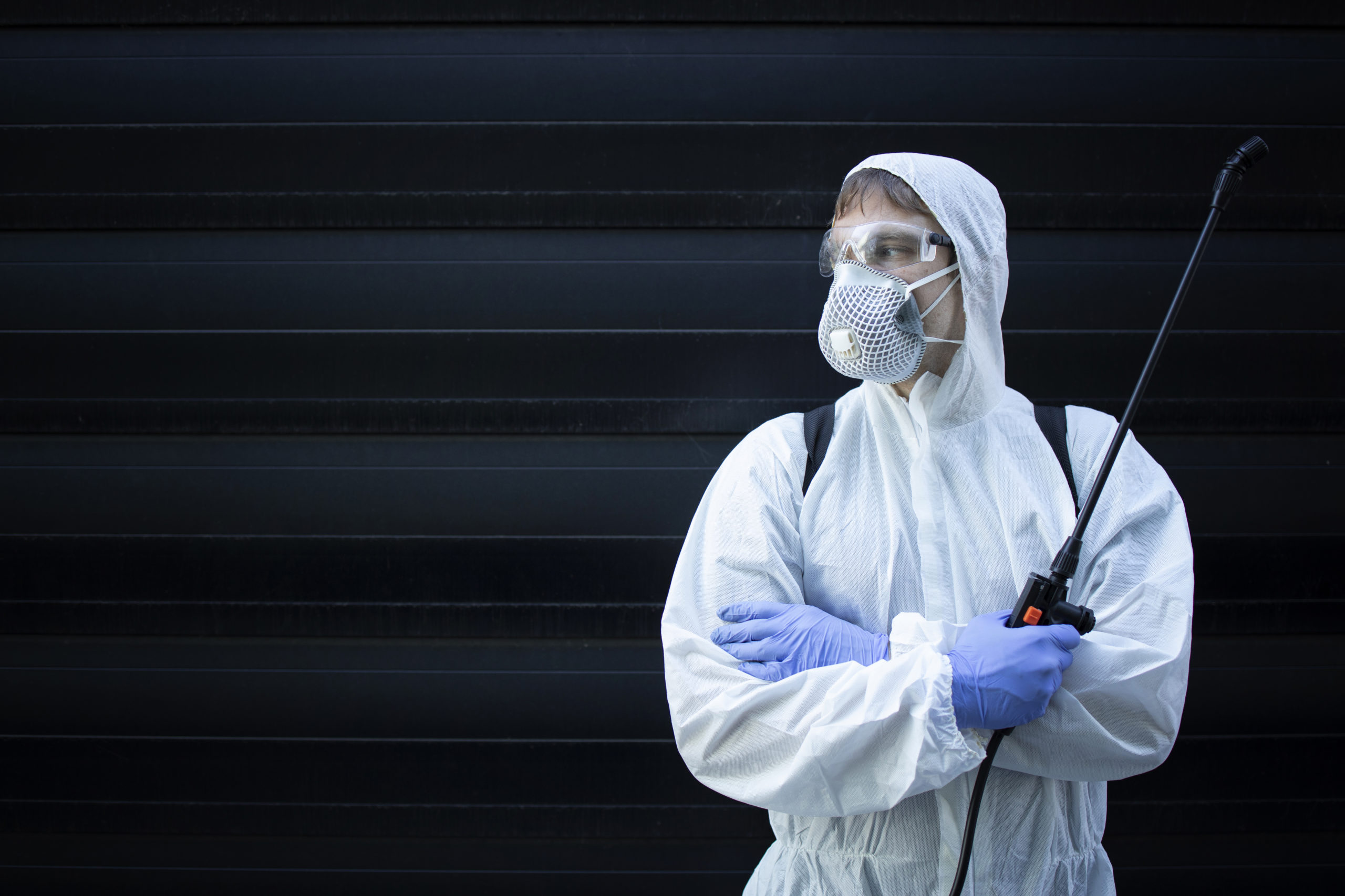 Portrait of professional exterminator holding sprayer with chemicals for pest control.